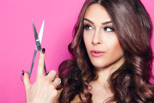 young woman with beautiful hair look at scissors in one hand studio shot pink background