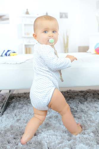 baby with dummy standing
