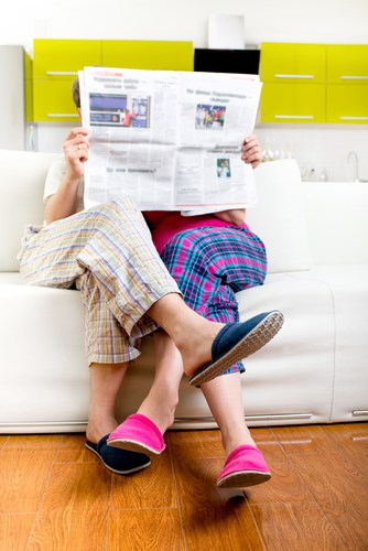 Married couple reading newspaper dressed in pajamas sitting in sofa at home