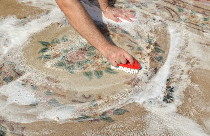 Washing carpet outside with red brush and soapy water, on a sunny day