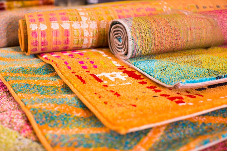 Various colourful wool rugs for sale at store